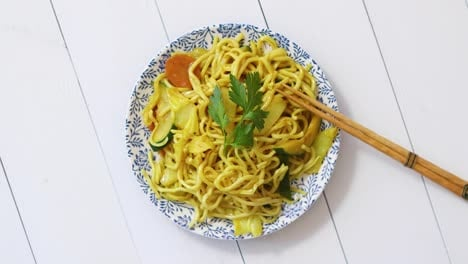 Traditional-Noodles-with-Chicken-and-vegetables-served-on-ceramic-plate-with-chopsticks-on-side