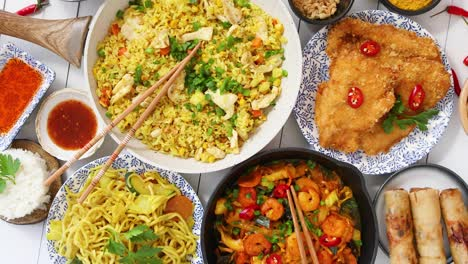 Asian-food-served-Plates-pans-and-bowls-full-of-noodles-chicken-stir-fry-and-vegetables