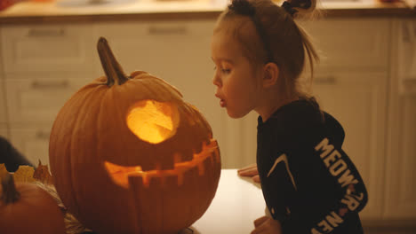 Girl-blowing-at-jack-o-lantern