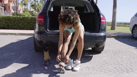 Woman-putting-roller-skates-while-sitting-in-car-trunk