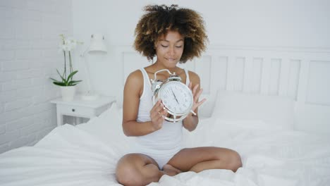 Charming-woman-posing-on-bed-with-clock