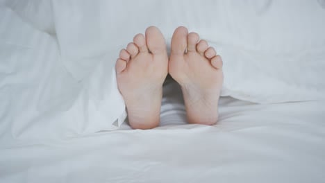 Crop-female-feet-under-blanket