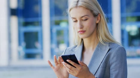 Young-businesswoman-using-smartphone-near-building