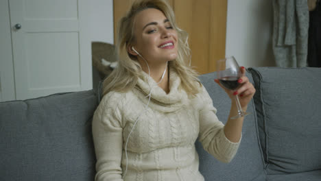 Smiling-woman-with-wine-listening-to-music