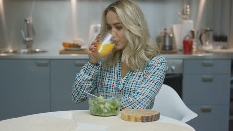 Woman-drinking-juice-and-eating-salad