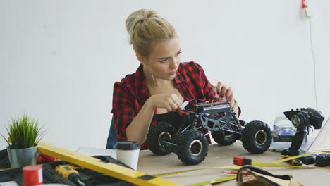 Female-repairing-radio-controlled-car-