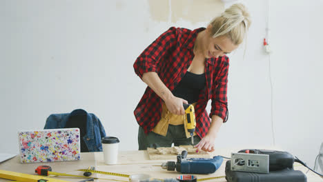 Female-drilling-wooden-plank-on-workbench-
