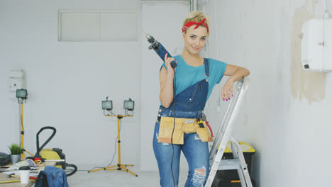 Woman-with-drill-standing-on-stepladder-