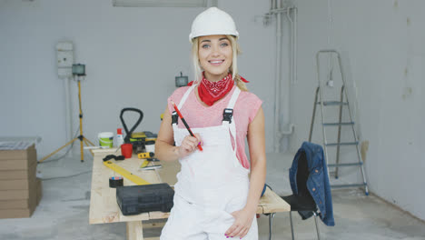 Smiling-female-carpenter-standing-at-workbench-