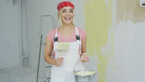 Cheerful-woman-with-brush-and-paint-bucket-