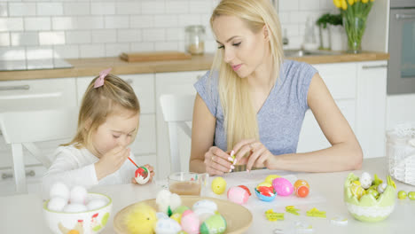Mother-looking-at-girl-coloring-eggs