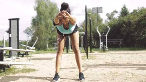 Sportswoman-warming-up-in-park