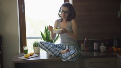 Young-woman-sitting-on-table-and-eating-breakfast