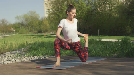 Slim-brunette-doing-yoga-twist-in-park