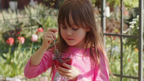 Cute-little-6-or-7-years-old-girl-eating-fruit-dessert-jelly-in-summer-garden-Slow-motion-video