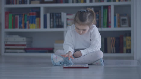 Interested-girl-with-tablet-on-floor