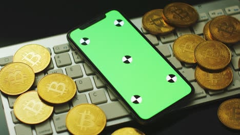 Smartphone-and-bitcoins-on-keyboard