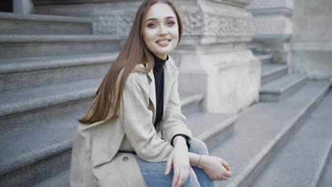 Young-stylish-female-wearing-jeans-and-coat-smiling-at-camera