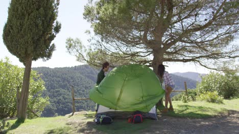 Two-travellers-putting-up-tent