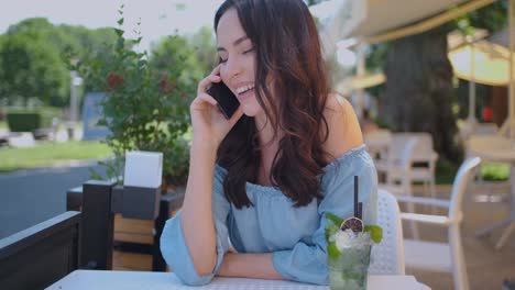 Pretty-brunette-woman-sitting-in-outdoor-restaurant-and-talking-her-mobile-phone