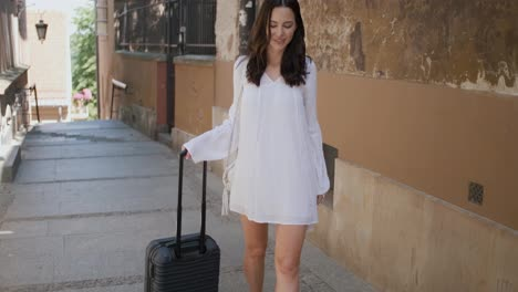 Beautiful-woman-walking-with-trolley-suitcase-in-small-street-in-the-city