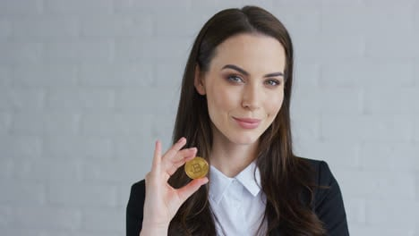 Businesswoman-showing-bitcoin-to-camera