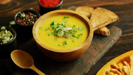 Fresh-pumpkin-soup-in-bowl-on-chopping-board