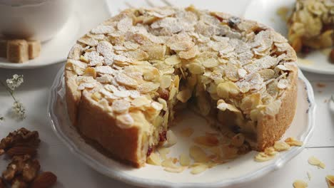 Whole-delicious-apple-cake-with-almonds-served-on-wooden-table