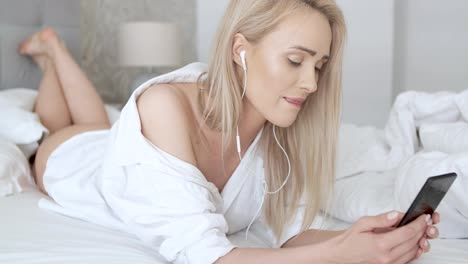 Beautiful-smiling-blond-woman-lying-in-white-bed-and-using-a-smartphone