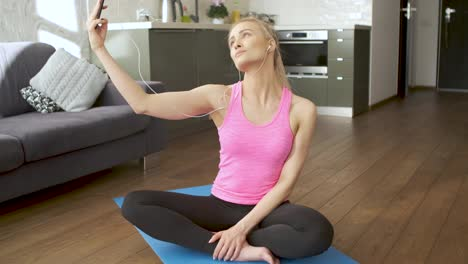 Young-attractive-sporty-woman-sitting-on-yoga-mat-making-selfie-with-her-mobile-phone