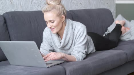 Happy-blond-woman-lying-prone-on-sofa-and-working-on-laptop-computer