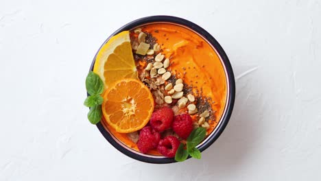 Bowl-with-fresh-healthy-smoothie-or-yogurt-With-orange-slices-tangerine-raspberry-chia-and-nuts