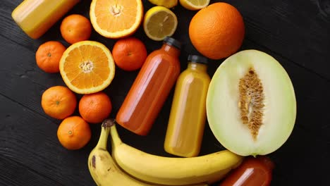 Mix-of-orange-and-yellow-colored-fruits-and-juices-on-black-wooden-background