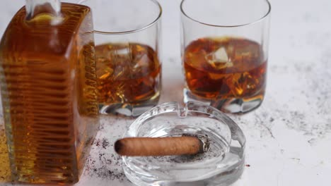 Bottle-and-glasses-of-brandy-or-wiskey-and-nice-big-cuban-cigar