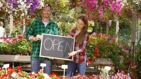 Two-florists-with-open-sign-in-their-shop