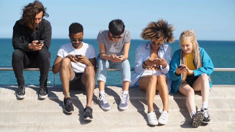 Contemporary-diverse-friends-with-smartphones-on-seafront
