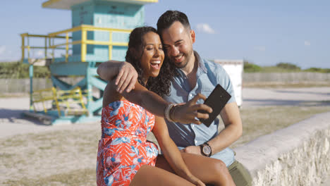 Excited-couple-taking-selfie-on-seafront