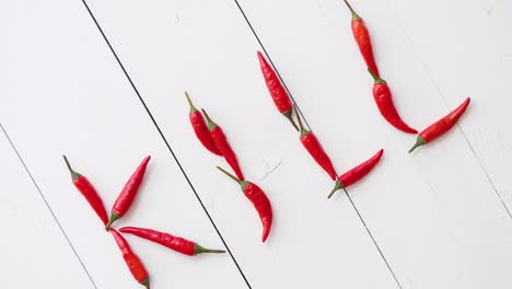 A-word-KILL-formed-with-small-red-chilli-peppers-Placed-on-white-wooden-table