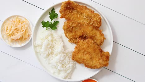 Crispy-chicken-fried-in-breadcrumbs-served-with-rice-View-from-the-top-on-white-wooden-background
