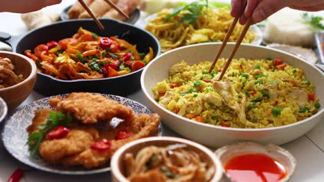 Family-meal-concept-with-asian-food-Plates-pans-and-bowls-full-of-tasty-oriental-dishes