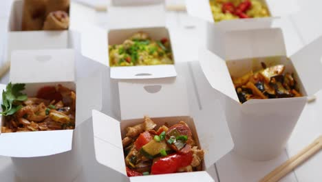 Asian-take-away-or-delivery-food-concept-Paper-boxes-placed-on-white-wooden-table