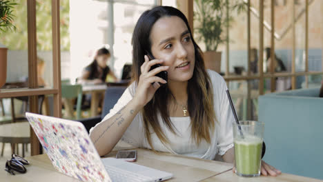 Young-woman-sitting-listening-to-a-mobile-call