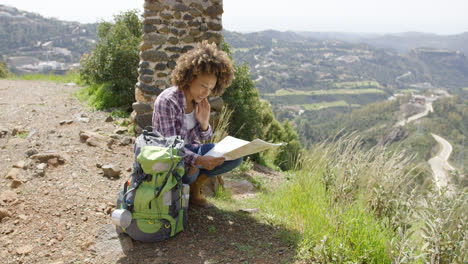 Young-female-sitting-with-backpack-and-map