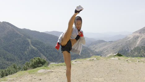 Young-female-kickboxer-in-mountains