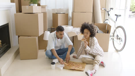 Hungry-young-couple-eating-a-pizza-on-the-floor