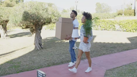 Young-couple-moving-house-carrying-boxes