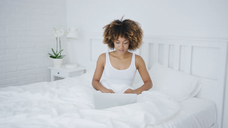 Charming-woman-with-laptop-in-bed