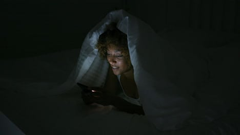 Young-woman-using-teléfono-in-dark-room