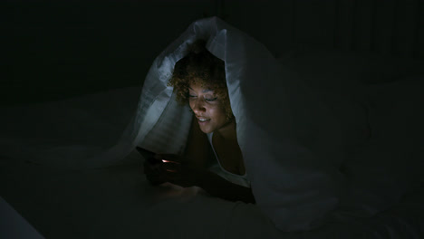Young-woman-using-phone-in-dark-room
