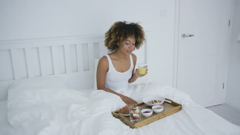 Woman-with-smartphone-in-bed-having-meal